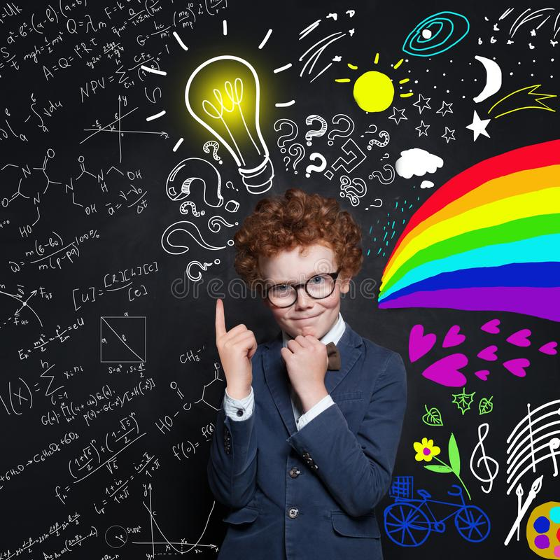 Cute child boy thinking and pointing up on lightbulb. Brainstorming and idea concept.  stock images
