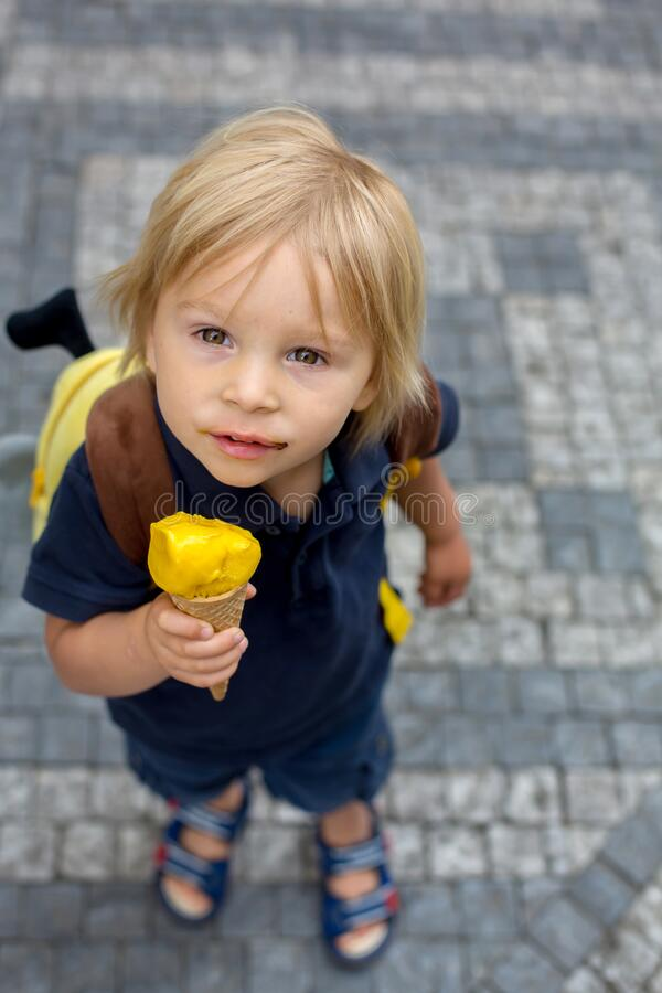 Cute child, boy, visiting Prague after the quarantine Covid 19, eating ice cream royalty free stock photo
