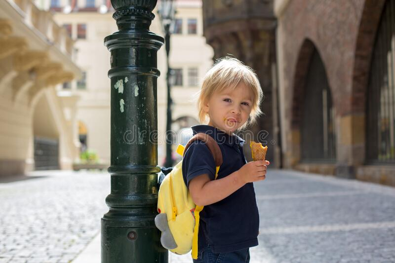 Cute child, boy, visiting Prague after the quarantine Covid 19, eating ice cream stock photo