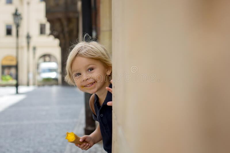 Cute child, boy, visiting Prague after the quarantine Covid 19, eating ice cream royalty free stock photography