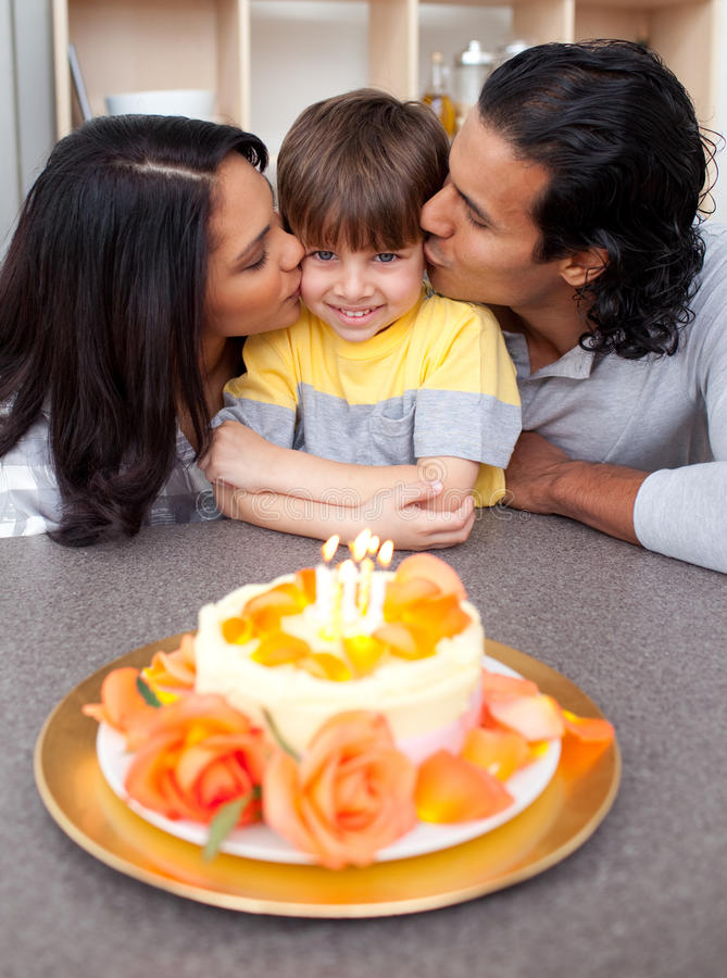 Cute child celebrating his birthday with parents. Cute children celebrating his birthday with parents kissing him in the kitchen royalty free stock photos