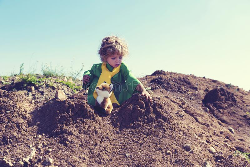 Cute child with curly blond hair playing with plush fox toy above pile of earth wearing green and yellow clothes. Selective focus royalty free stock photos
