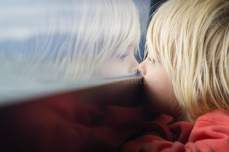 Cute child deep in thought. Cute young child deep in thought looking out of a window stock photos