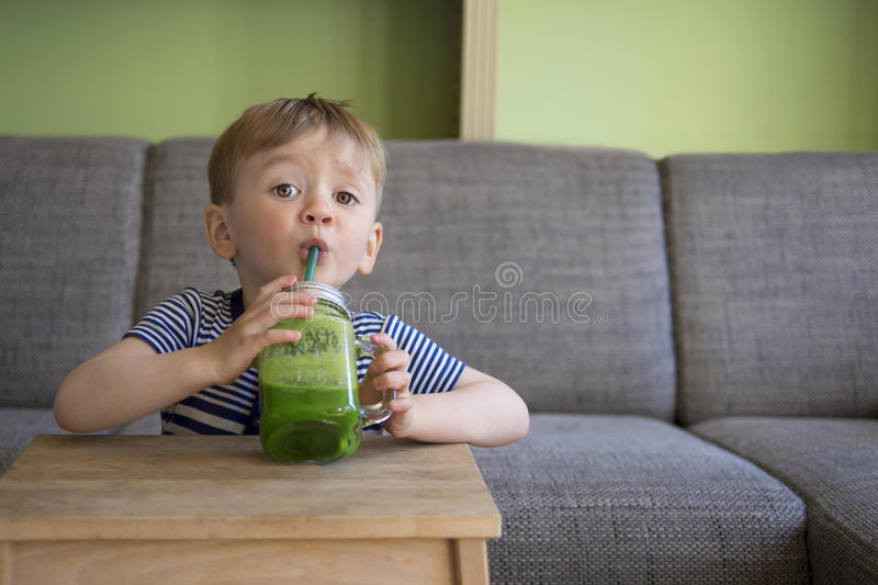 Cute child drinking a green smoothie stock images