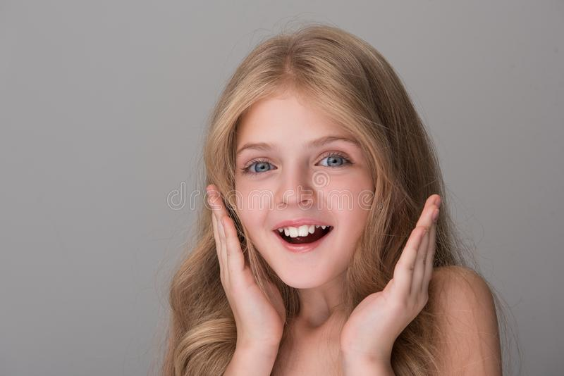 Cute child is expressing wonder and joy. Cannot believe. Close-up portrait of surprised lovely girl is standing and smiling while looking at camera with stock photos