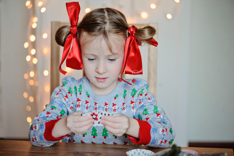 Cute child girl in christmas sweater making post cards. Cute child girl in christmas sweater and with red bows making post cards stock photo