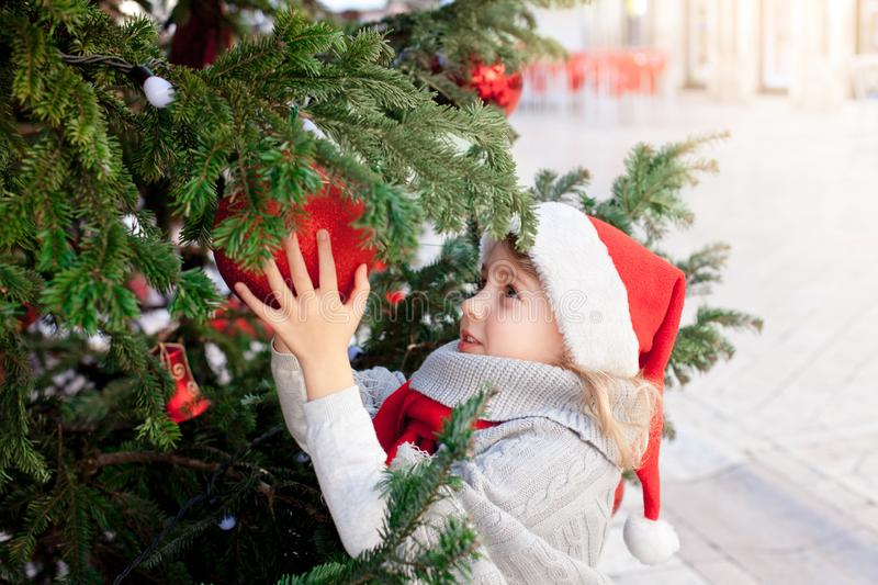 Cute child girl is decorating Christmas tree with ornaments outside. Little kid in santa hat stock photos