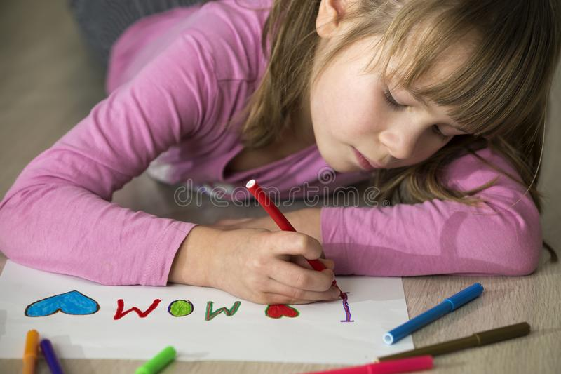 Cute child girl drawing with colorful crayons I love Mom on white paper. Art education, creativity concept royalty free stock photo