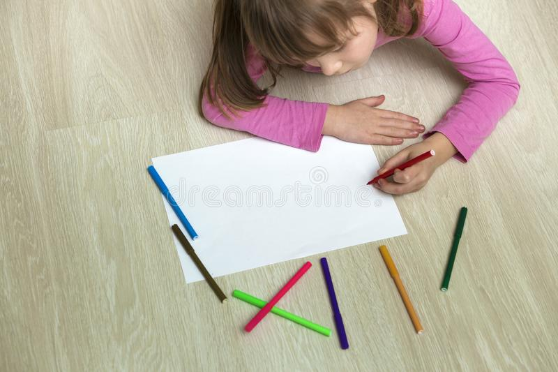Cute child girl drawing with colorful pencils crayons on white paper. Art education, creativity concept royalty free stock photos