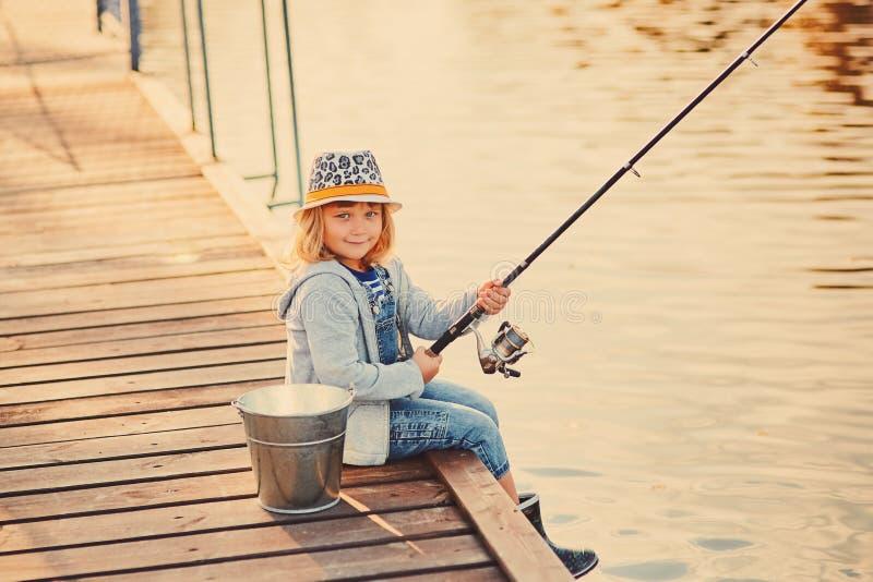Cute child Girl Fiing från träpier på en sjö Familjefritid under sommarsoliga dagar en liten flicka som har kul av en arkivfoto
