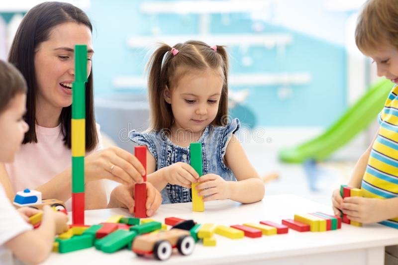 Cute child girl with group of children and carer in the learning center stock photo