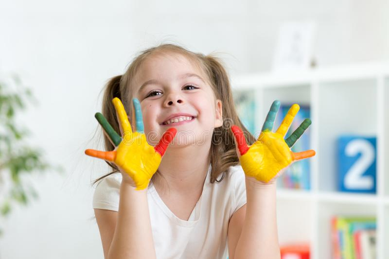 Cute child girl have fun coloring her hands royalty free stock image