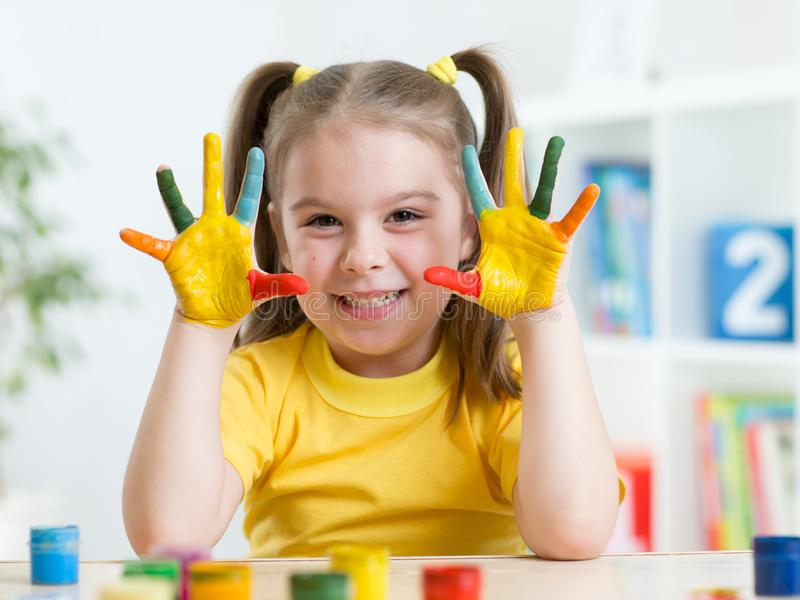 Cute child girl have fun painting her hands royalty free stock image
