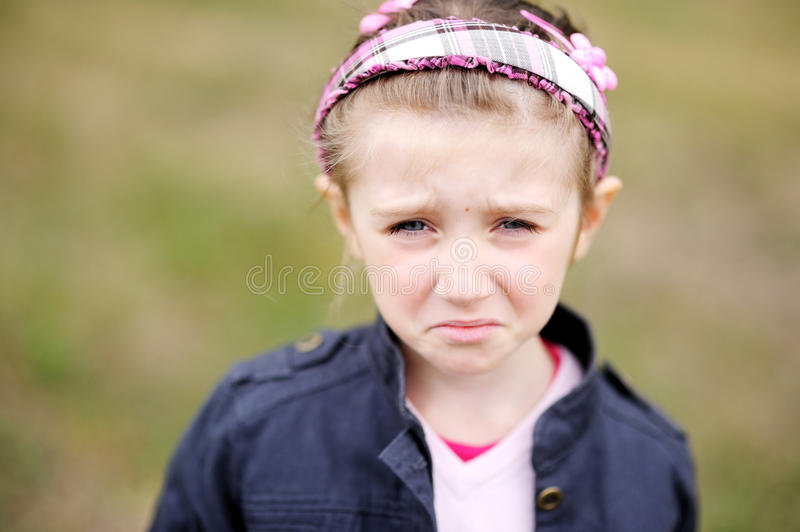 Cute child girl makes upset weepy face royalty free stock image