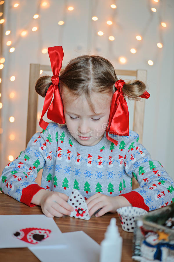 Cute child girl making Christmas post cards. Cute child girl in knitted swetaer making Christmas post cards stock images
