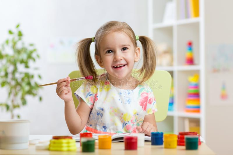 Cute child girl painting picture on home interior background stock image