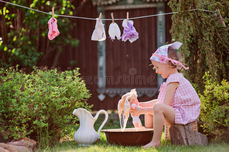 Cute child girl in pink dress playing toy wash in sunny summer garden royalty free stock photography