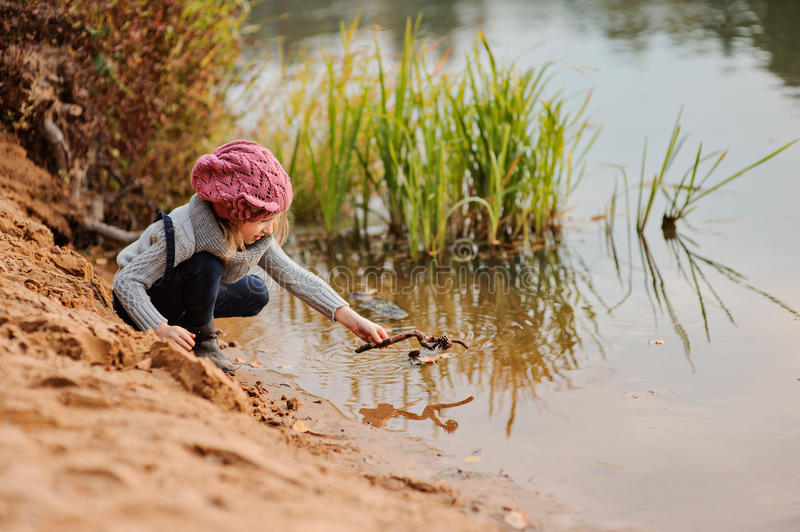 Cute child girl in pink knitted hat plays with stick on river side with sand beach. Cute child girl in pink knitted hat and grey sweater plays with stick on stock photos