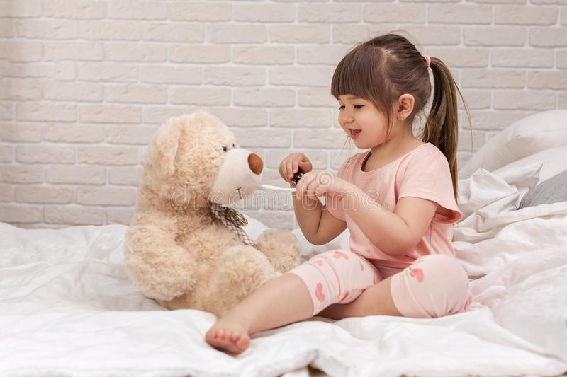 Cute child girl playing doctor with teddy bear stock photos
