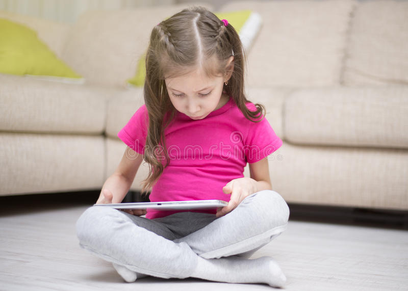 Cute child girl playing with a tablet computer. royalty free stock photography