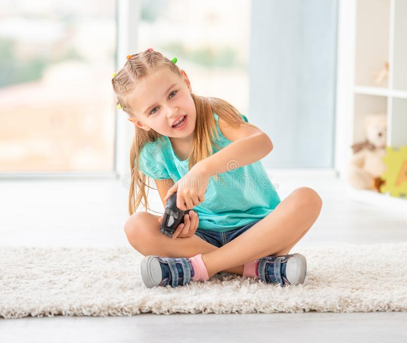 Cute child girl playing video games on console royalty free stock photo