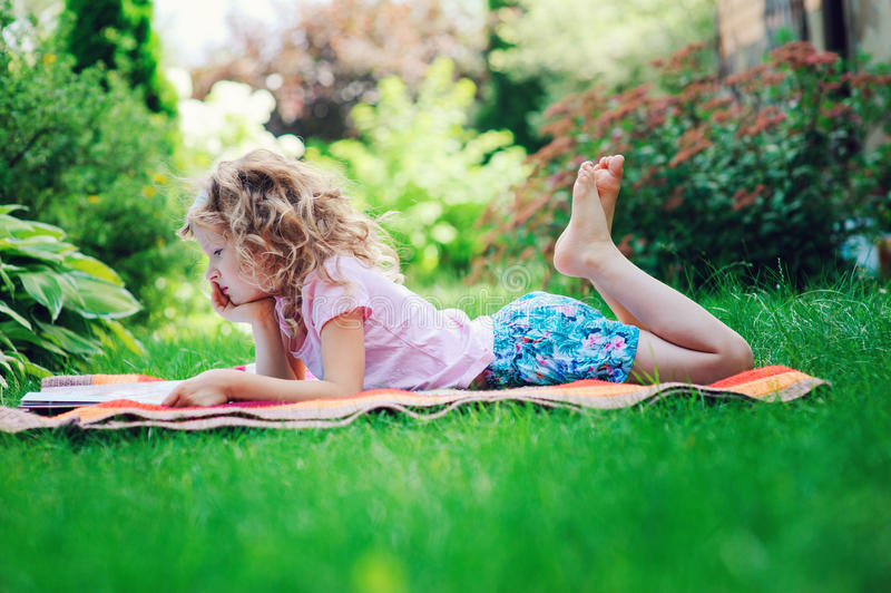 Cute child girl reading book in summer garden outdoor royalty free stock photo