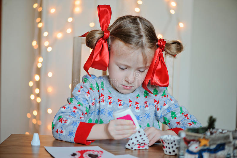 Cute child girl in seasonal sweater making Christmas post cards. With light on background stock photography