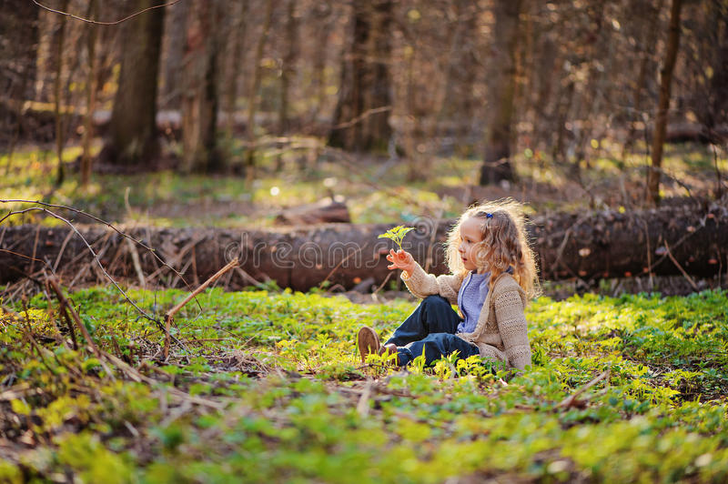 Download Cute Child Girl Sitting In Green Leaves In Early Spring Forest Stock Photo - Image: 48840706