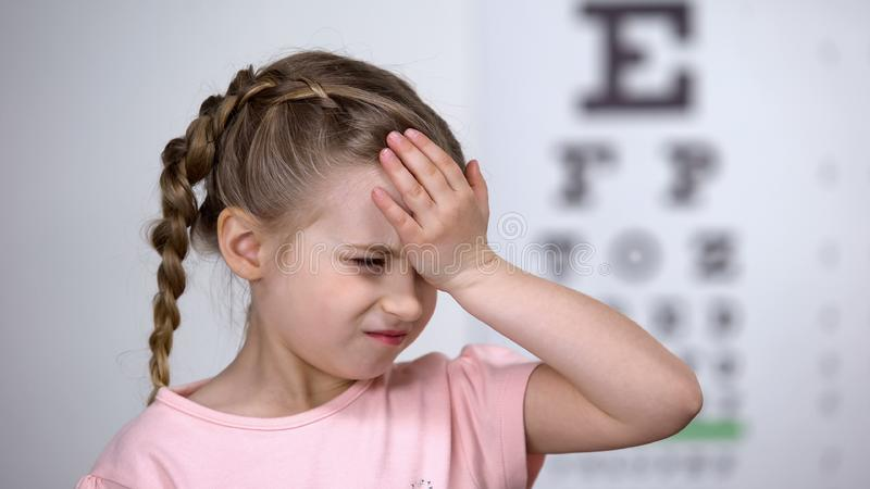 Cute child girl suffering headache, first myopia symptom, loss of eyesight. Stock photo stock photo