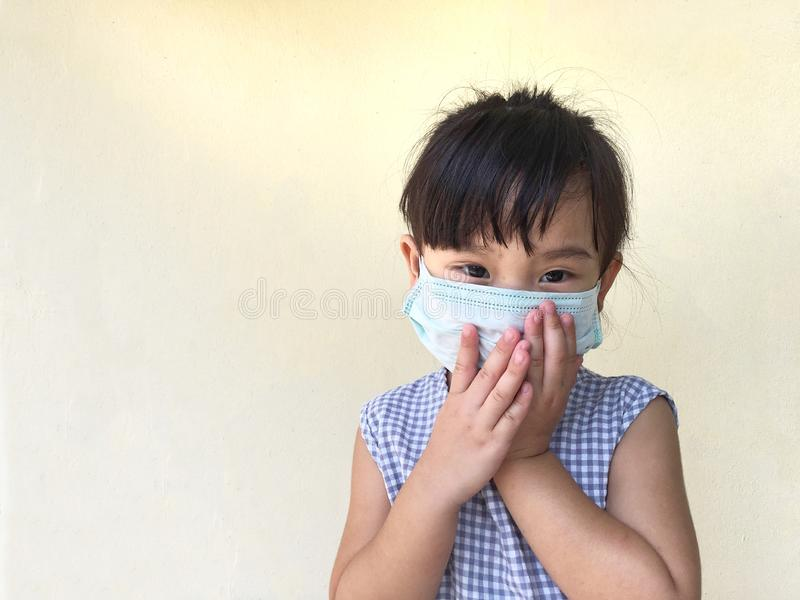Cute child girl wearing a mask to prevent dust and germs. Isolated on cream background royalty free stock photography