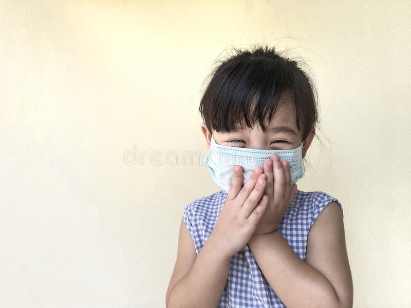 Cute child girl wearing a mask to prevent dust and germs. Isolated on cream background stock image