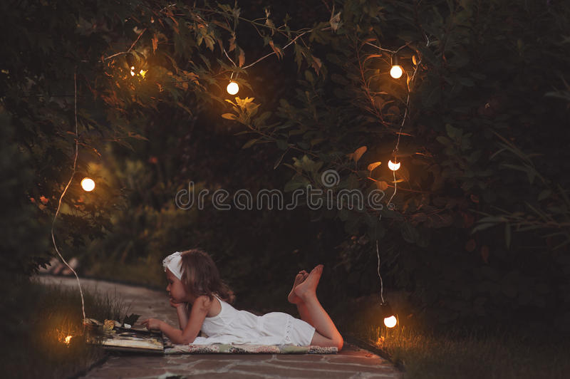 Cute child girl in white dress reading book in evening summer garden with lights decorations. Cute child girl in white dress reading book in evening summer warm royalty free stock image