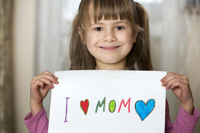 Cute child girl wit sheet of paper with colorful crayons painted words I love Mom. Art education, creativity concept stock images