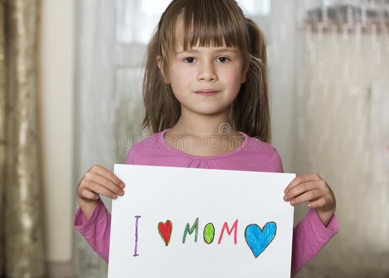 Cute child girl wit sheet of paper with colorful crayons painted words I love Mom. Art education, creativity concept royalty free stock image