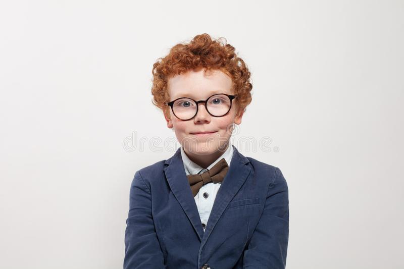 Cute child in glasses and blue suit portrait. Funny redhead boy on white background stock images