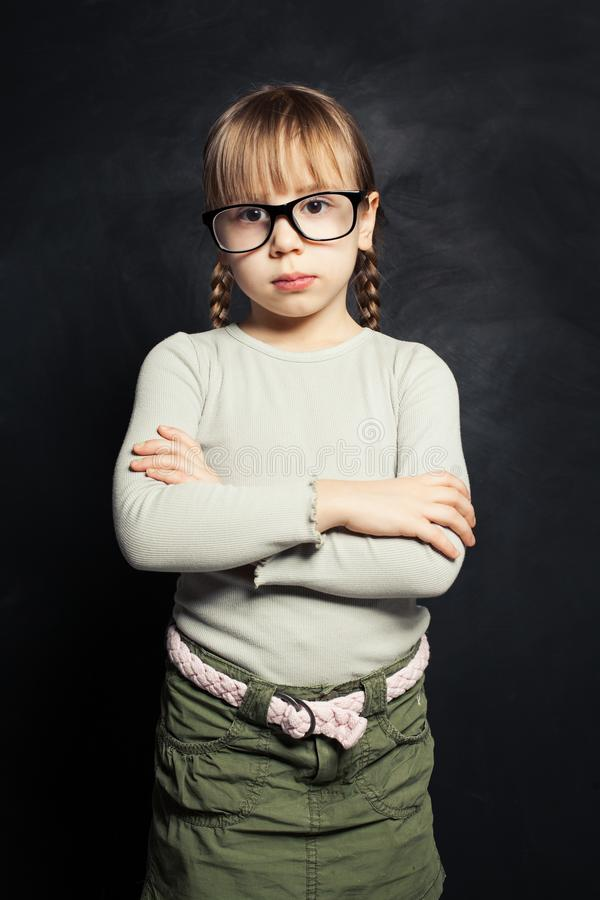 Cute child in glasses thinking against school classroom blackboard background stock image