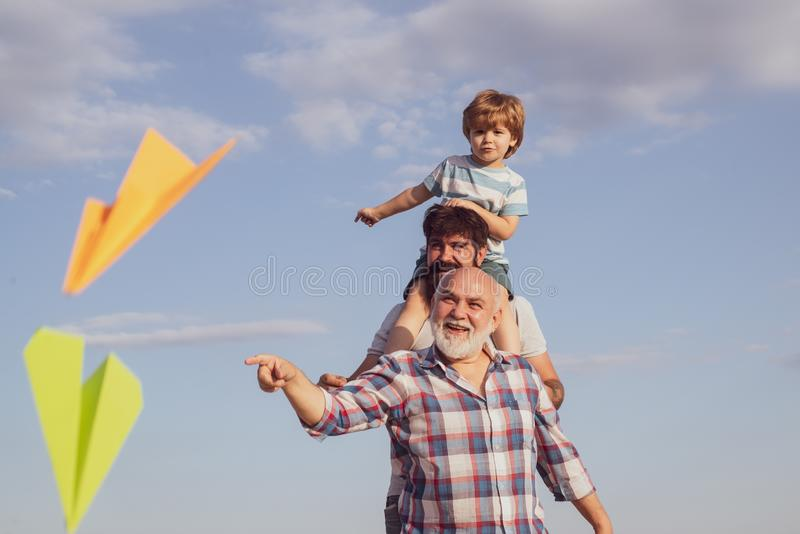 Cute child hugging his father and grandfather. Happy family. Airplane ready to fly. Happy three generations of men have royalty free stock image