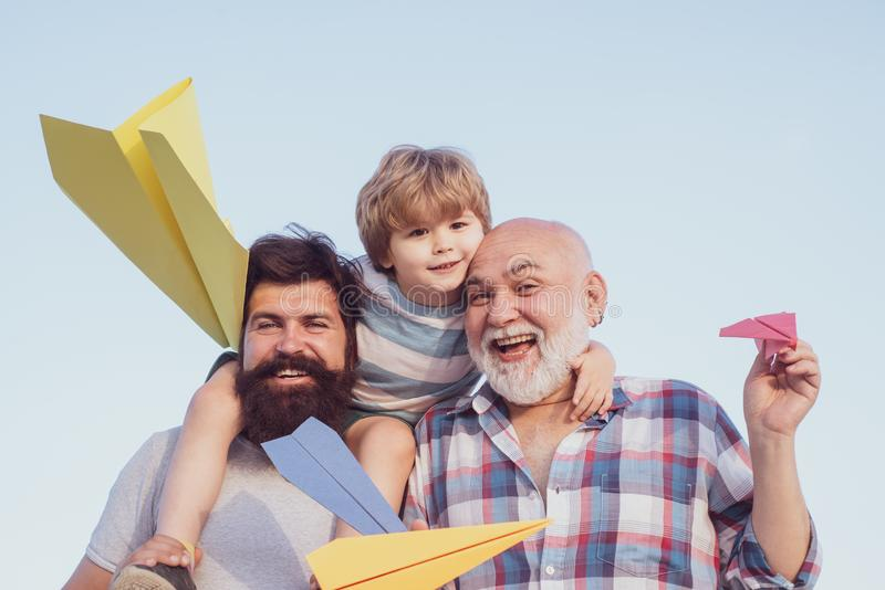 Cute child hugging his father and grandfather. Three different generations ages: grandfather father and child son stock photos