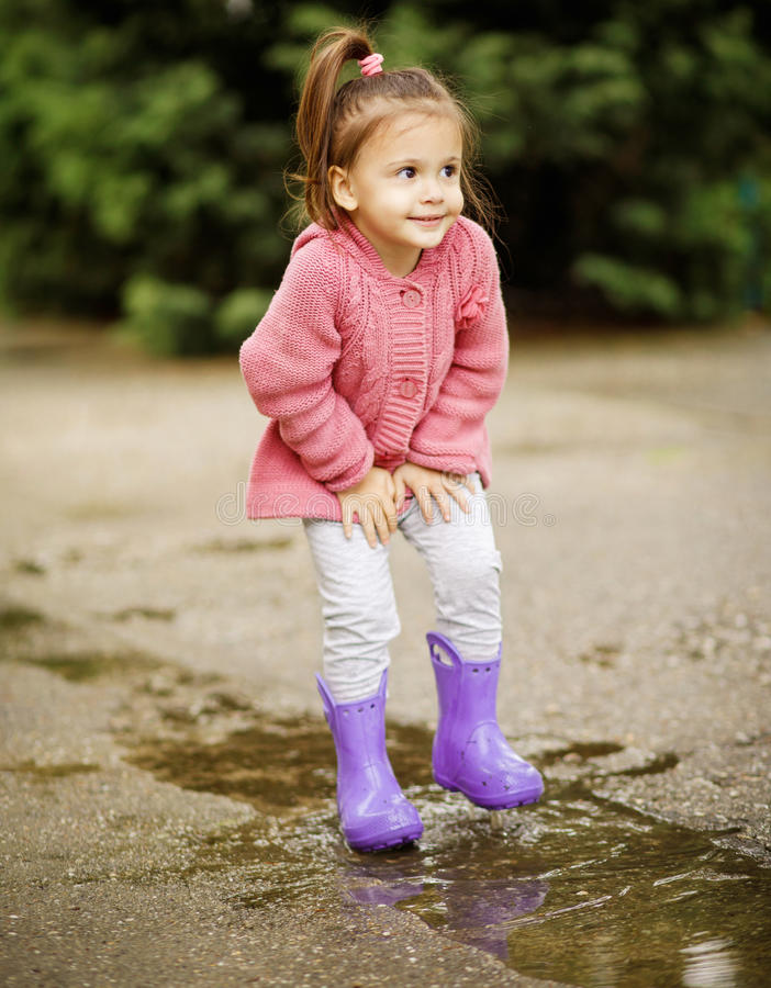 Cute child jumping in a puddle of water at the summer or autumn. Day stock photo