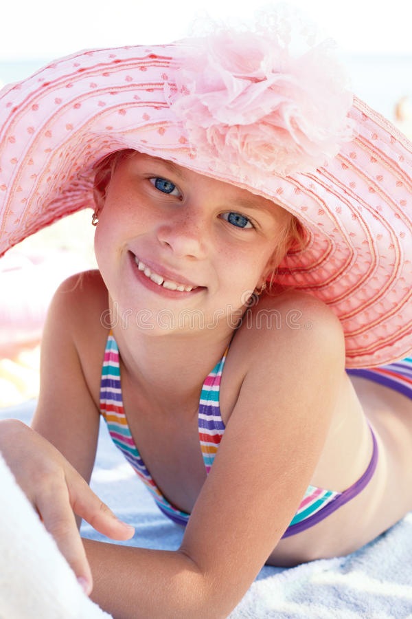 Cute child lying down on deckchair of beach resort. Happy cute child lying down on deckchair of beach resort royalty free stock photography