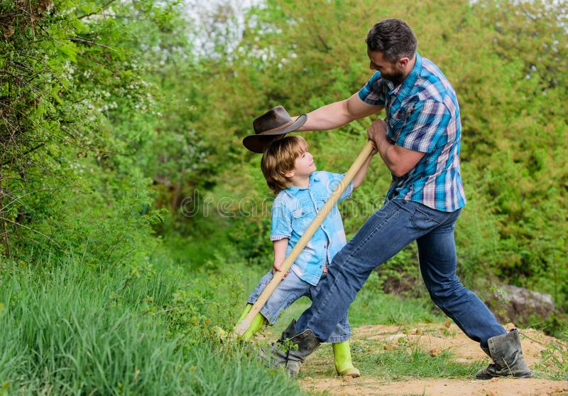 Cute child in nature having fun cowboy dad. Find treasures. Little boy and father with shovel looking for treasures stock image