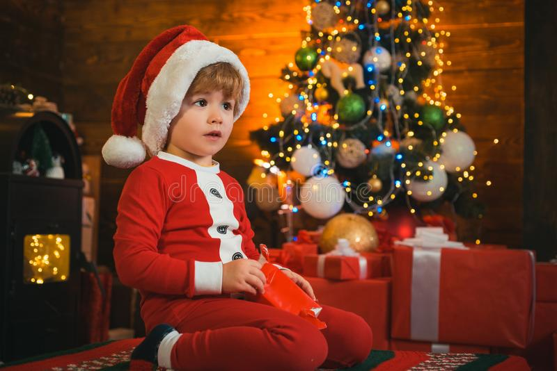 Cute child opening christmas gift. Lovely baby enjoy christmas. Santa boy little child winter celebrate at home. Boy stock images