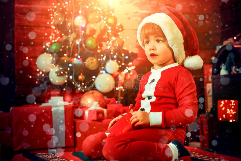 Cute child opening christmas gift. Lovely baby enjoy christmas. Santa boy little child winter celebrate at home. Boy stock photo