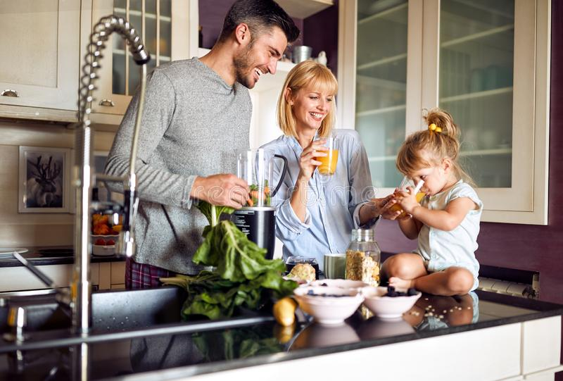 Child with parents drinking orange juice in kitchen stock photo