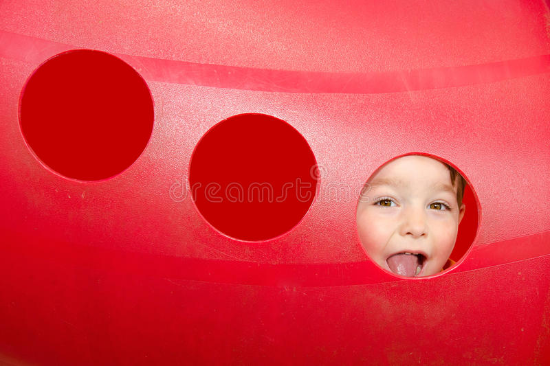 Download Cute Child Peeks Through Hole At Playground Stock Photo - Image: 25402878