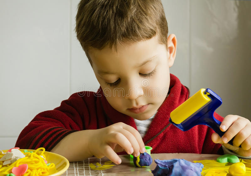 Cute child playing with plasticine stock photo