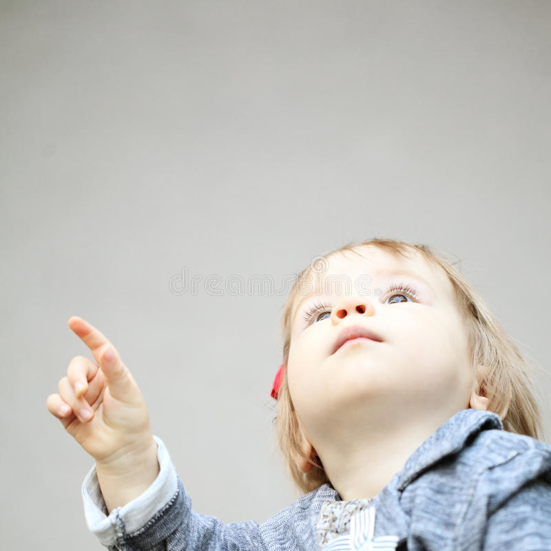 Cute child pointing and looking up stock photos