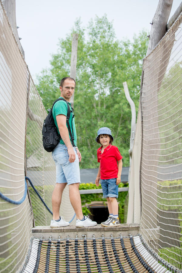Cute child, preschool boy, climbing in a rope playground structure with his father royalty free stock photo