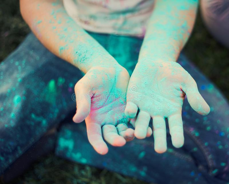 Cute child`s hands dirty because of colorful powder stock images