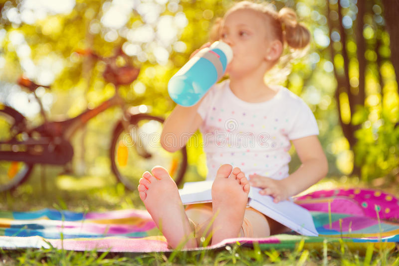 Cute child sitting on grass with book. Foots in focus stock images